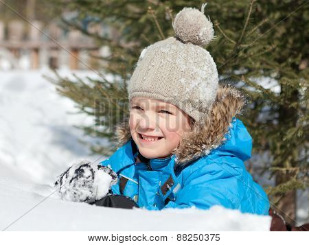 Boy In Winterwear Playing In Snowdrift