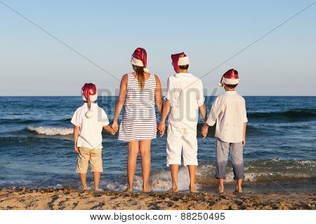 Children In Santa Claus Hat Are Standing On Beach