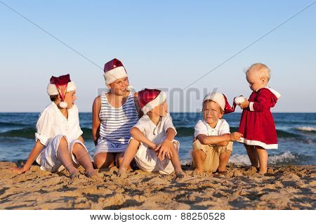 Children In Santa Claus Hat Are Sitting On Beach