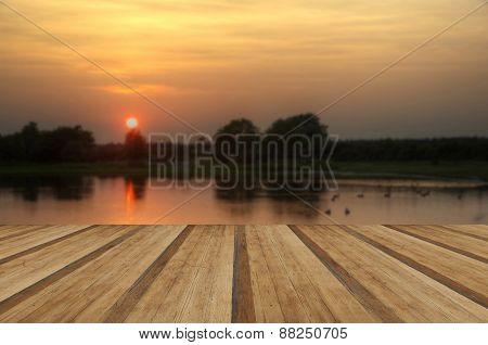 Setting Sun Glows Through Trees And Reflected In Still Lake Water With Wooden Planks Floor