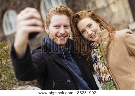 Couple Taking Photo With Mobile Phone