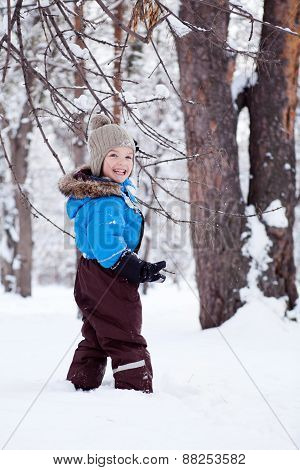 Portrait Of Cheerful Boy In Winter Forest