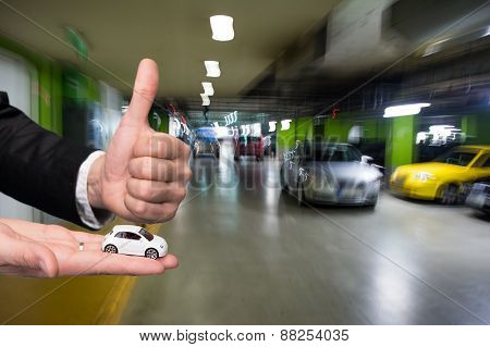 businessman in black suit holding small car model and showing ok sign