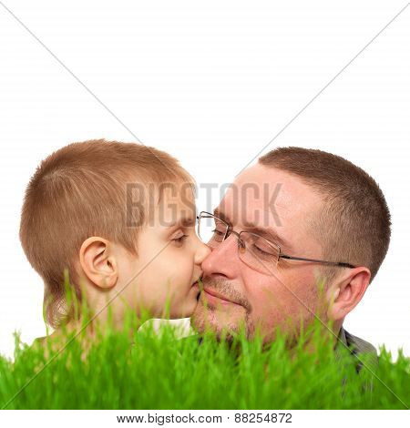 kid kissing parent, father's day, green grass, on white background