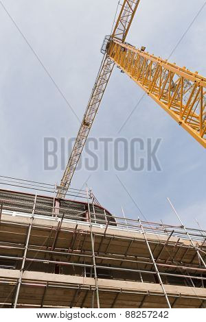 A view looking up to yellow tower crane on a construction site with concrete and steel structure