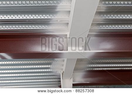 a red steel column intersecting a beam on the underside of a standard metal profiled deck
