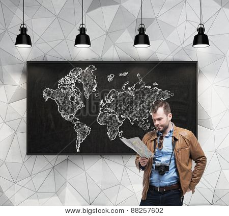Handsome Tourist Is Examining The Map In Front Of Chalkboard With The World Map Sketch