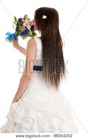 beautiful woman with a bouquet of flowers is standing back