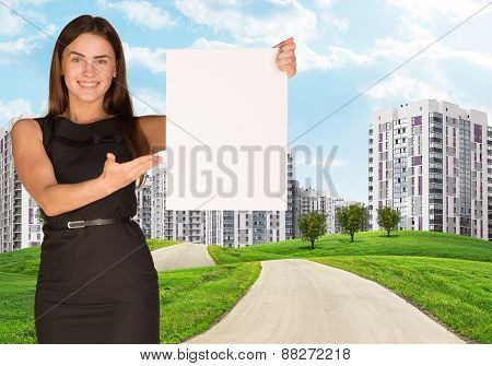 Estate agent holding blank poster with city on background