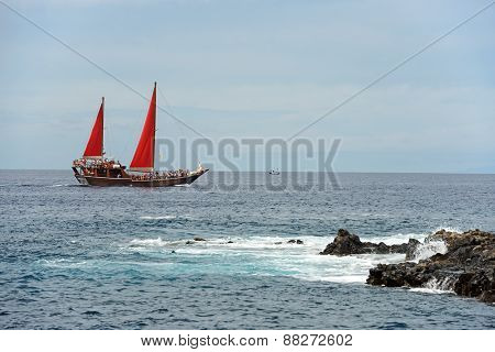 Yacht Under Red Sails Is Passing Along In The Sea.