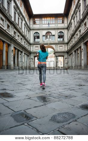 Fitness Woman Jogging Near Uffizi Gallery In Florence, Italy. Rear View