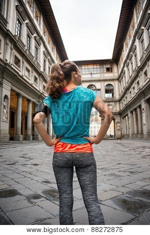 Fitness Woman Standing In Front Of Uffizi Gallery In Florence, Italy. Rear View