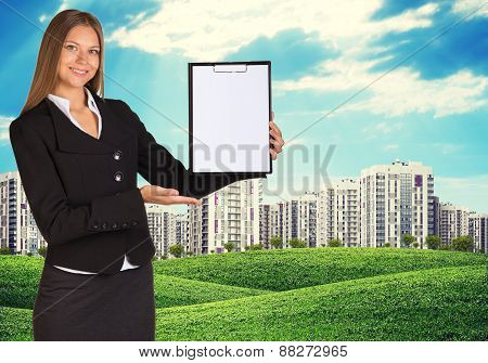 Young woman holding paper holder with nature and city on back