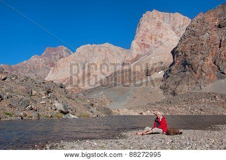 Man resting on the shore majestic mountain lake in Tajikistan