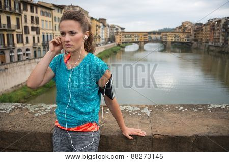 Fitness Woman Listening Music In Front Of Ponte Vecchio In Florence, Italy