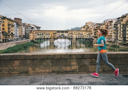 Fitness Woman Jogging In Front Of Ponte Vecchio In Florence, Ita
