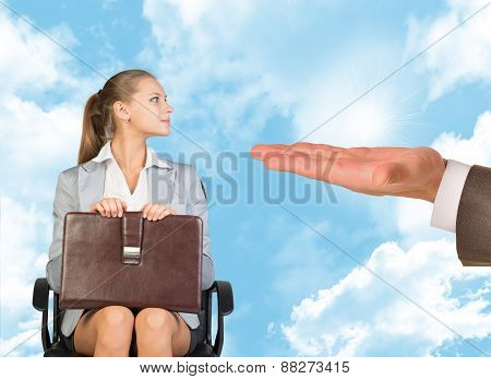 Young woman sitting in chair and looking at offering hand