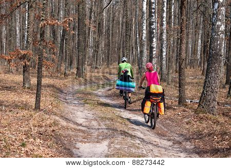 Man, woman and child practicing mountain bikes on a forest trail.