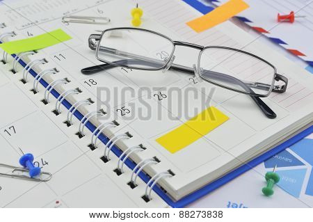 Monthly Planner With Glasses And Post It On Paper Graph