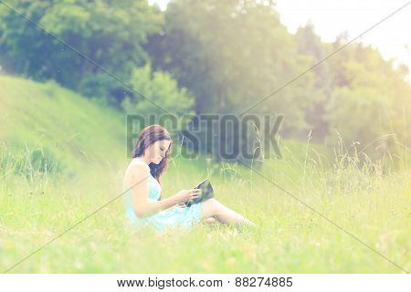 Girl sitting reading a book outdoors