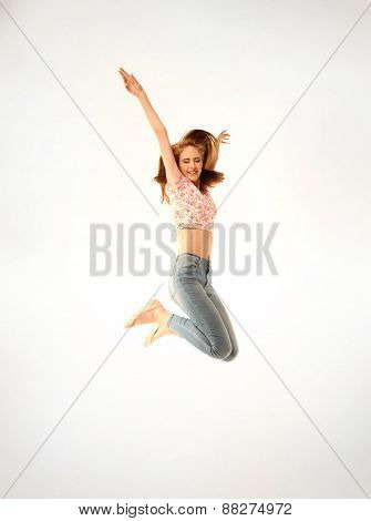 young girl with jeans and pink top jumping energetically