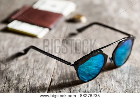 Stylish sunglasses with blue tinted mirror on textured wooden ba