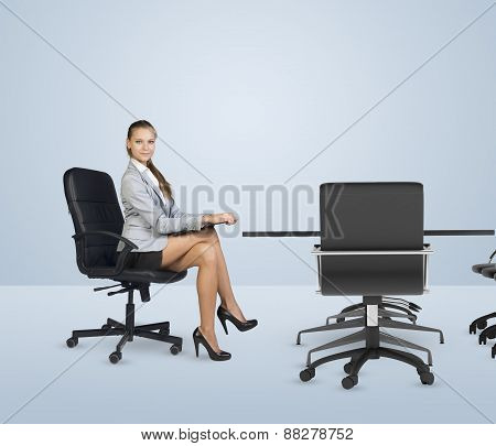 Businesslady sitting half-turned at table with folder in her hands