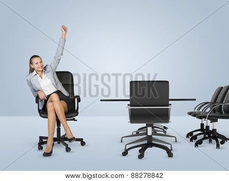 Smiling businesswoman sitting in chair and raising left hand