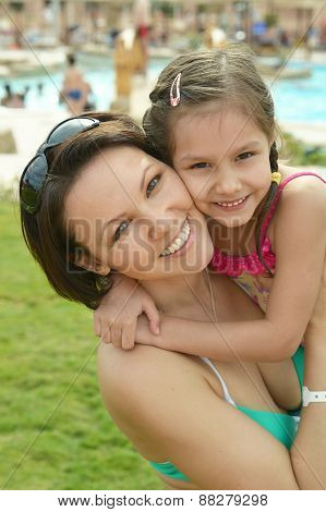 Mother with daughter near pool