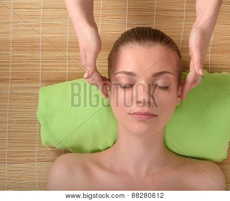 Beautiful young woman getting relaxing head massage. Top view