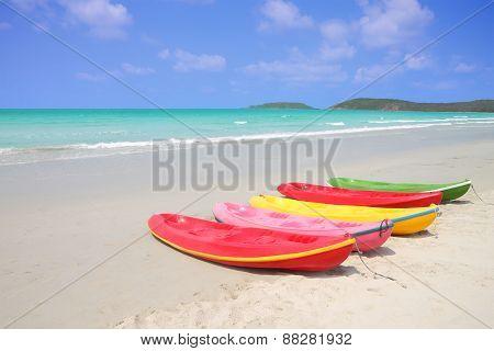 Multiple color kayaks rest on tropical beach.