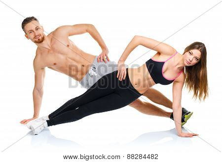 Athletic Attractive Couple - Man And Woman Doing Fitness Exercises On The White