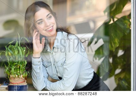 Woman Sitting Indoor In Urban Cafe Looking Through The Window