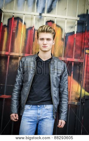 Attractive blond haired young man standing outdoors