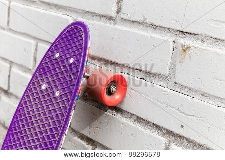 Modern Purple Skateboard Stands Near Brick Wall