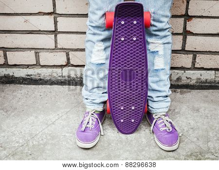 Teenager Girl In Jeans  Holds A Skateboard