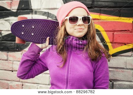 Blond Smiling Girl Stands Near By Wall With Skateboard