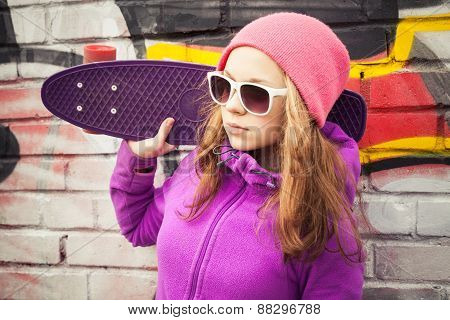 Blond Smiling Girl Stands Near A Wall With Skateboard