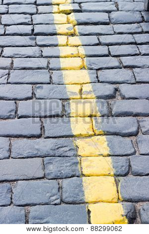 The yellow line on the road receding the stone