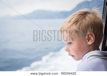 The boy looks at the sea from the deck of the ship