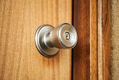 pic of keyholes  - Shining metal door handle with keyhole in closed wooden door photo with selective focus and shallow DOF - JPG