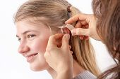 picture of ear  - Woman inserting a hearing aid into a young girl - JPG