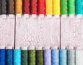 picture of lurex  - Bobbins with colorful threads on old wooden table background - JPG
