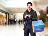 image of mall  - Smiling handsome man with shopping bags and credit card at the shopping mall - JPG