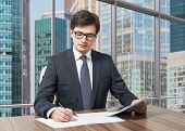 stock photo of diligent  - Handsome legal consultant is dealing with due diligence process in a modern skyscraper office with a panoramic Moscow city view. ** Note: Shallow depth of field - JPG