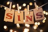 stock photo of envy  - The word SINS printed on clothespin clipped cards in front of defocused glowing lights - JPG