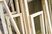 stock photo of framing a building  - Unwanted window frames with white wood and intact glass