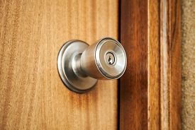 stock photo of keyholes  - Shining metal door handle with keyhole in closed wooden door photo with selective focus and shallow DOF - JPG