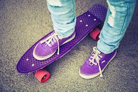 foto of skateboard  - Young skateboarder in gumshoes and jeans standing on his skate - JPG