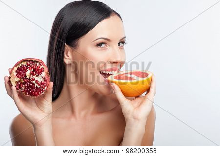 Attractive young woman is eating exotic fruit